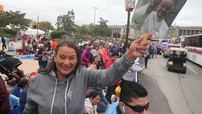Milagros Bobadilla of Somerville waves a photo of Pope Francis in Philadephia, Sunday, September 27, 2015, prior to a celebration of mass by the Pope Francis at the World Meeting of Families 2015.