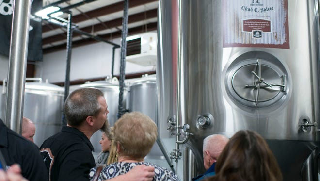 Mispillion River Brewing co-founder Eric Williams, left, looks up at the dedicated fermenter tank alongside Chad Spicer's mother Ruth Ann Spicer in a ceremony at the brewery Thursday, Feb. 26 in Milford.