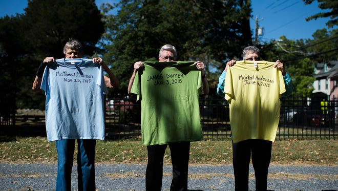 (From left) Karin Sannwald, Harry Forrest and Carol Suplee hold shirts Wednesday at Medford Friends Meeting with names of individuals who died from gun violence.