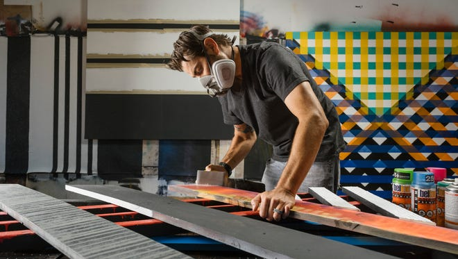 Artist Ryan Campbell works on a line segment work in his Cathedral City studio.