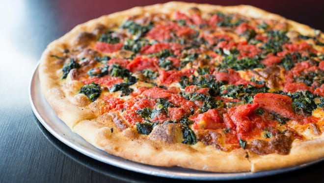 A signature white pie with spinach and chopped tomatoes from Tacconelli's Pizzeria in Maple Shade.