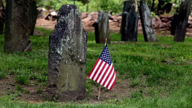 A flag is planted at the grave of a military veteran at the Clarkstown Reformed Church cemetery in West Nyack, photographed May 18, 2016.