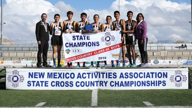Navajo Prep's boys cross-country team and coaches pose with the state championship trophy and banner on Saturday in Rio Rancho.
