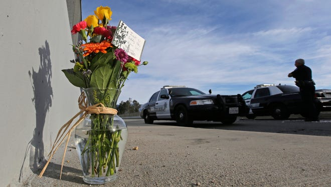 Flowers are left by the side of the road as a San Bernardino police officer blocks the road leading to the site of the Dec. 2 mass shooting in San Bernardino, Calif.  President Barack Obama plans to meet with families of victims of the mass shooting, the White House said Wednesday.