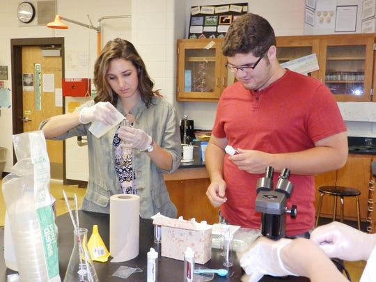 Morgan Gifford (left) and Steven Carlaw, students at Cumberland Regional High School, test water samples for coliform bacteria.
