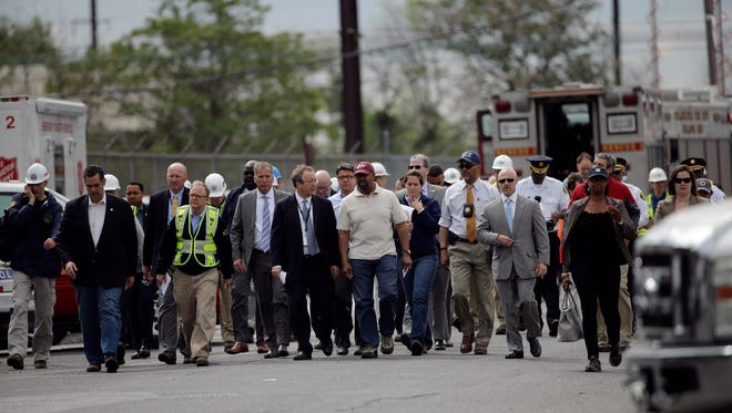 Philadelphia Mayor Michael Nutter, center in maroon hat, walks to a news conference with other emergency and transportation officials near the scene of a deadly train derailment, Wednesday, May 13, 2015, in Philadelphia. An Amtrak train headed to New York City derailed and crashed in Philadelphia on Tuesday night killing at least six people and injuring dozens more. (AP Photo/Matt Slocum)
