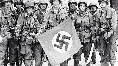A 101st Airborne Division soldier poses with a captured Nazi flag in this World War II.