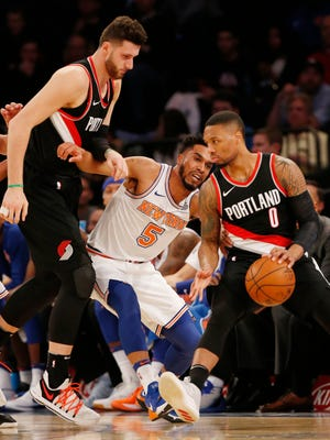 New York Knicks guard Courtney Lee (5) tries to push his way through Portland Trail Blazers center Jusuf Nurkic (27) and Trail Blazers guard Damian Lillard (0), who drives to the basket during the first half of an NBA basketball game in New York, Monday, Nov. 27, 2017.