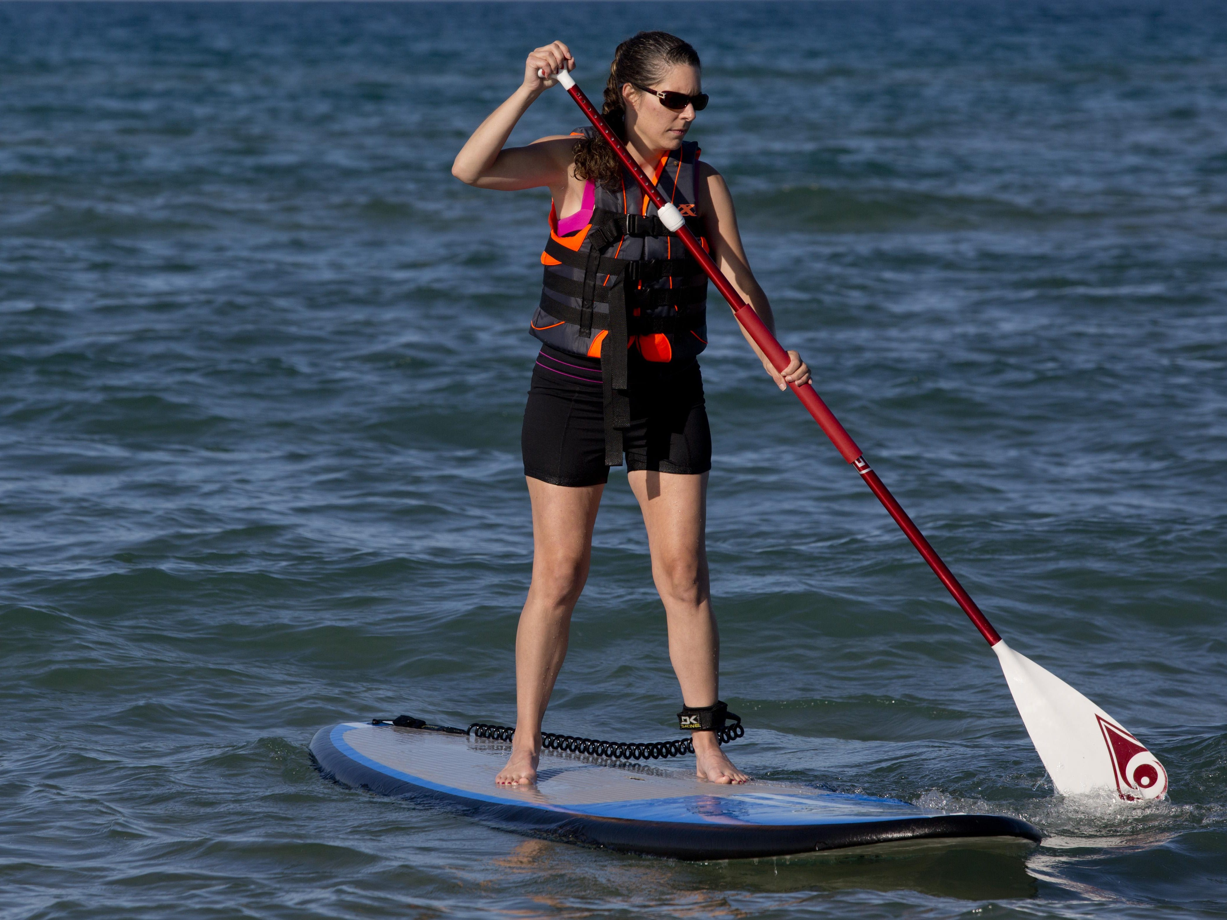 Julie Wiley, of Port Huron, paddles during a stand up paddle board class Wednesday, July 22, 2015 at Lakeside Beach in Port Huron.