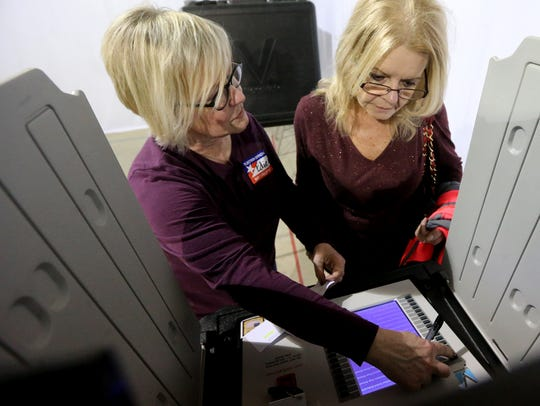 Poll worker Edie Urness-Pondillo, left walks Gail Frye,right,
