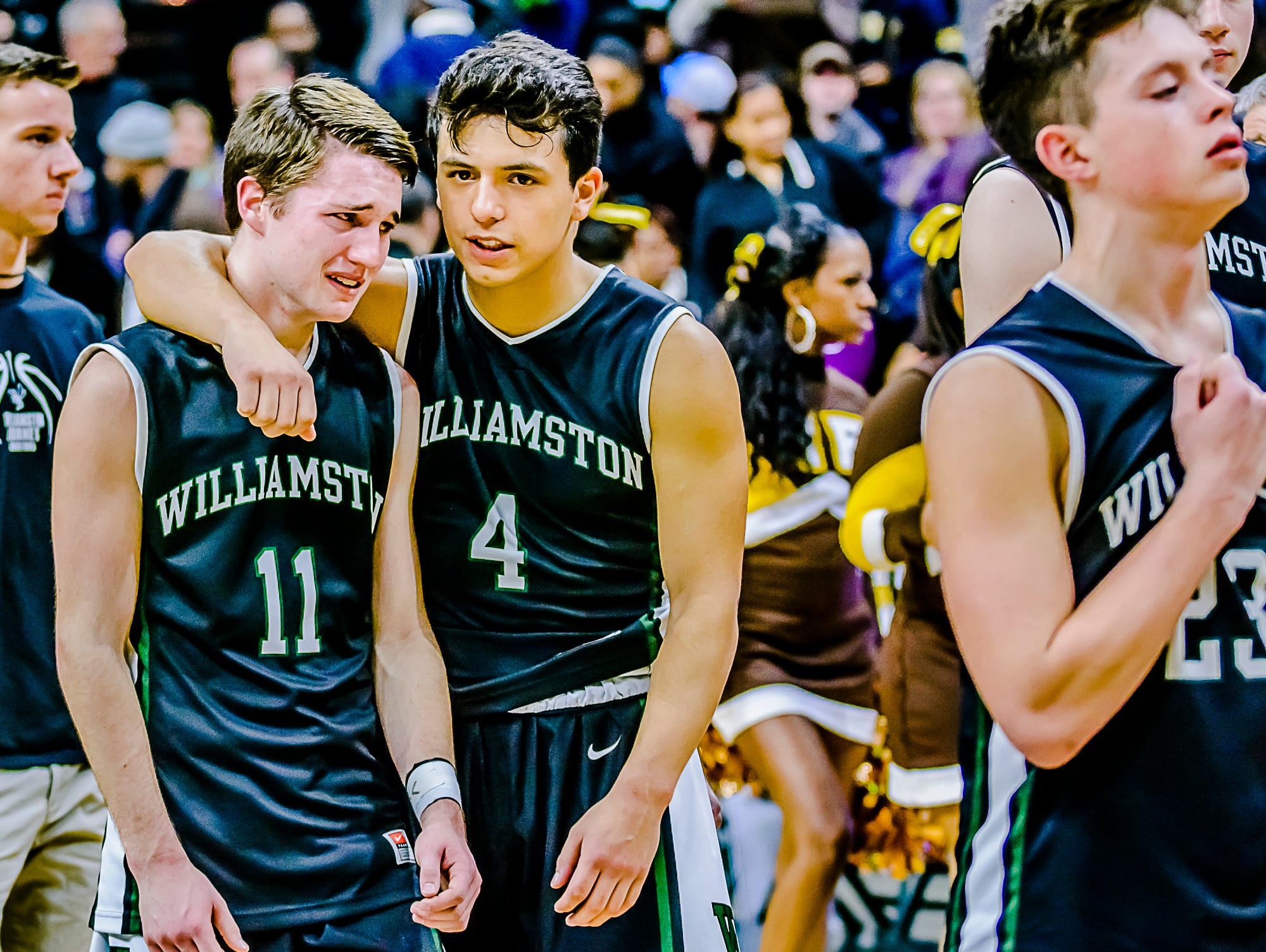 Sophomore Frankie Toomey ,4, of Williamston consoles senior Connor Porrell ,11, after their Class B state semifinal loss to Detroit Henry Ford Friday March 25, 2016 at the Breslin Center in East Lansing. KEVIN W. FOWLER PHOTO