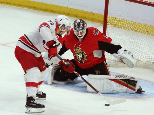 Carolina Hurricanes' Jeff Skinner (53) backhands a shot to score against Ottawa Senators' goaltender Mike Condon (1) during third-period NHL hockey game action in Ottawa, Ontario, Saturday, March 24, 2018. (Fred Chartrand/The Canadian Press via AP)