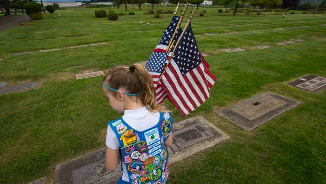 Girl Scout Genevieve Blakley looks for the grave of a military veteran May 26 at West Lawn Cemetery in Eugene, Ore. Blakey is adding an American Flag to each grave of a service man  or woman buried there in honor of Memorial Day.
