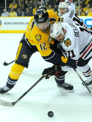 Predators center Mike Fisher (12) and Blackhawks center Andrew Desjardins (11) fight for a faceoff.