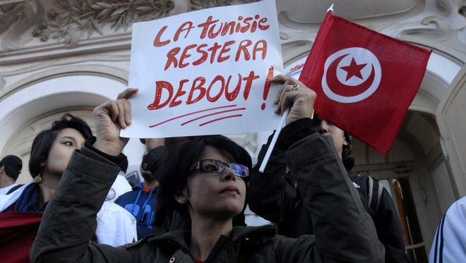 "A Tunisian woman holds a placard reading in French ""Tunisia will remain standing"" as she takes part in a rally March 18, 2015, a few hours after an attack on the National Bardo Museum."