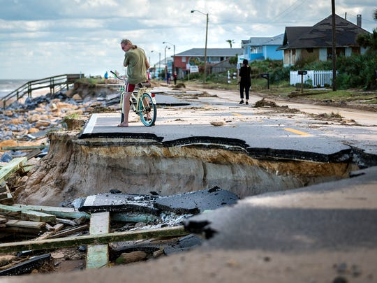"Kevin O'Connor, of Long Beach, N.Y., surveys a section of State Road A1A damaged by erosion after Hurricane Matthew passed the east coast of Florida in October. O'Connor said he owns two homes in Flagler Beach and came down to try to protect his investments. ""If this were a direct hit, we wouldn't be standing here. Twenty or 30 years ago when I first started coming here, the beach was way deep, but now, the last 10 years after those other storms, there is nothing left,"" O'Connor said."