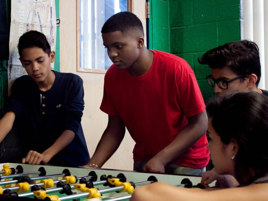 "Franklin ""Kinte"" Gilbert, winner of the Boys and Girls Club of America New Mexico Youth of the Year Award, center, plays foosball at the Las Cruces Boys and Girls Club alongside Edgar Ramirez, right, as Josheph Gallardo, left, and Amaya Aguilar, right, watch. June 15, 2016"