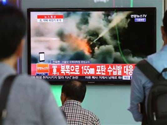 "People watch a television news program reporting about South Korea's respond to the North with a file video footage at Seoul train station in Seoul, South Korea, Thursday, Aug. 20, 2015. South Korea's military fired dozens of shells Thursday at rival North Korea after the North lobbed a single artillery round at a South Korean border town, the South's Defense ministry said. The letters read ""South Korean military, respond 155mm shells to the North."""