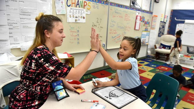 First grade teacher Lisa Imperato (left) celebrates the progression of student Timaiya Elkins Wimberly during word work lessons inside her classroom on Thursday Dec. 15, 2016, at Weatherbee Elementary School in Fort Pierce. Ms. Imperato used the crowdfunding website DonorsChoose.com to raise funds to buy five Kindle Fire tablets, with cases and headphones, for her students.