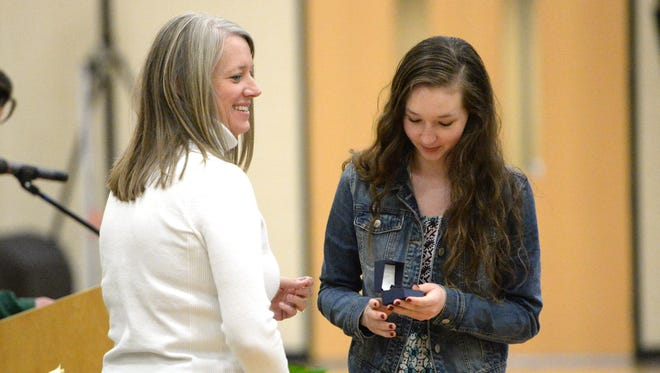 Cassidy Davis (right) receives her state championship ring from Wilson Memorial principal Kelly Troxell Thursday night at a ceremony in the school's gym.