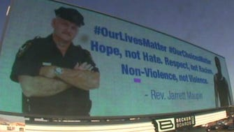 A billboard spreading aiming to spread a message of understanding between police and blacks is seen from a freeway on Wednesday.