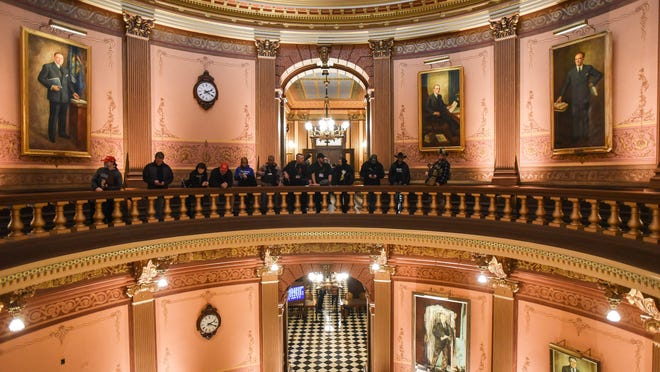 Armed ralliers protest in the rotunda inside the Michigan Capitol on Thursday. April 30, 2020.