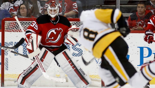 Penguins defenseman Brian Dumoulin (8) takes a shot on Devils goalie Cory Schneider during the second period of Tuesday's game, in Newark.
