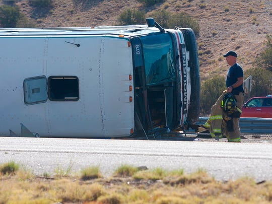 An officer works at the scene of a deadly multi-vehicle crash involving a bus that occurred on Interstate 25, north of Bernalillo, N.M., on Sunday, July 15, 2018.