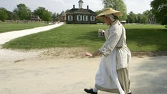 A worker dressed in colonial-era walks through colonial
