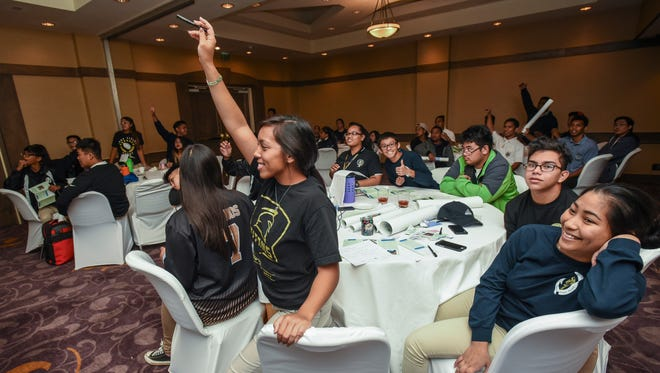 Tiyan High School junior Kai Perez rises from her seat in an attept to answer a question for points during a quiz on local food systems at the 8th Regional Island Sustainability Conference, hosted by the University of Guam, at the Hyatt Regency Guam in Tumon on April 18, 2017.