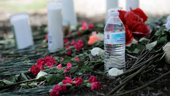 A bottle of water, flowers, candles and stuffed animals help form a makeshift memorial in the parking lot of a Walmart store near the site where authorities Sunday discovered a tractor-trailer packed with immigrants outside a Walmart in San Antonio, Monday, July 24, 2017. Several people died and others hospitalized after being crammed into a sweltering tractor-trailer in the midsummer Texas heat, according to authorities in what they described as an immigrant-smuggling attempt gone wrong.