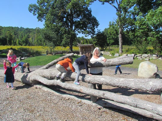 Sandy Dixon, director of the Hudson Highlands Nature Museum's Nature-based preschool and Early Childhood Action in Nature project manager, with preschoolers in Grasshopper Grove, the Museum's nature play area.