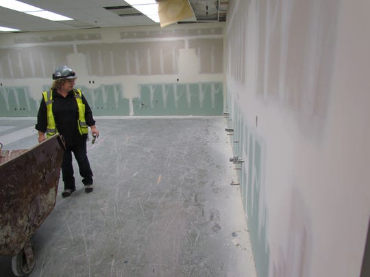 Assistant Project Manager Diana Kessler looks over a gutted classroom in the process of a makeover at Stayton High School. When the school year begins, this will be a fully equipped science laboratory.