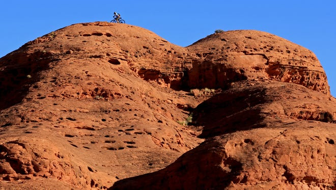 A mountain biker crosses the slickrock above the Church Rocks Trail.