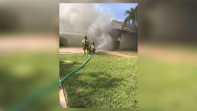 Palm Beach County Fire Rescue crews work to extinguish a fire in a garage at a home in the Boca Woods Country Club. No injuries were reported.