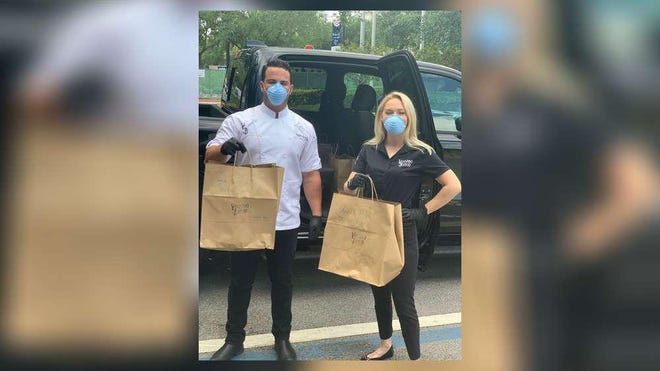 """Voodoo Bayou Executive Chef Angelo Arboleda (left) and Marketing Manager Dana Hardy helped deliver 20 """"Taste of New Orleans"""" lunches to the Palm Beach Gardens Police Department Wednesday as part of an effort to support first responders who are on the front lines of the coronavirus pandemic."""
