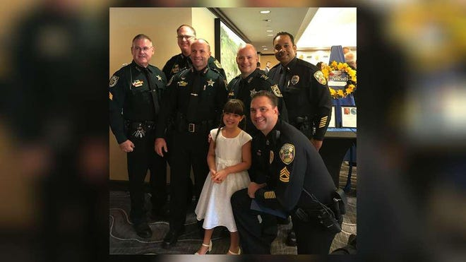 Bailee Bonick, 9, poses with police officers during a Law Enforcement Appreciation Luncheon at PGA National Resort & Spa. Bailee, a longtime singer who performed at the event, created a YouTube video that pays tribute to first responders.