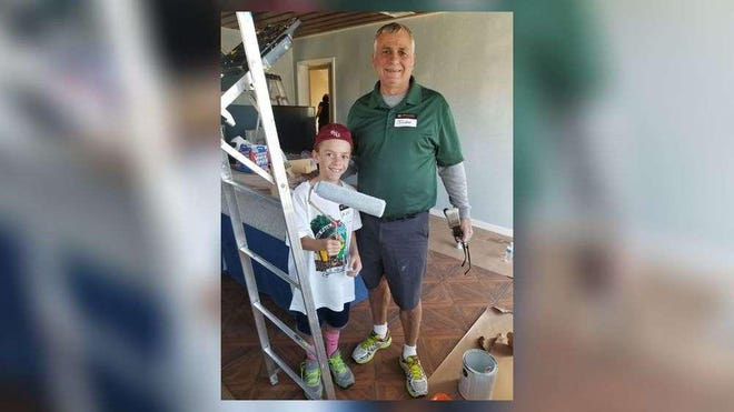 As part of a community project called Fourth Saturday Serve, mentor John and mentee Alex, help paint a house in Riviera Beach.