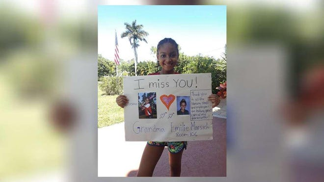 Emilie Dupoux, 9, holds a poster she made for her grandmother, who is a resident at Royal Palm Beach Health and Rehabilitation Center. Her father, Serge Dupoux, said the poster is hanging on the door to the facility, where a worker tested positive for COVID-19 on April 24.