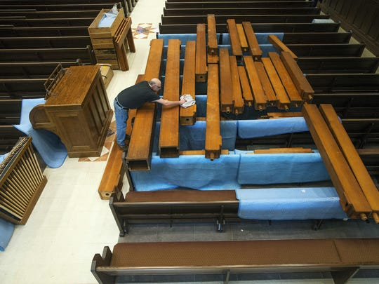 Craig Manor of Otsego-based Lauck Pipe Organ Co. dusts off large wooden pipes before hoisting them to the balcony for installation into a pipe organ at the Cathedral of Mary of the Assumption in Saginaw.