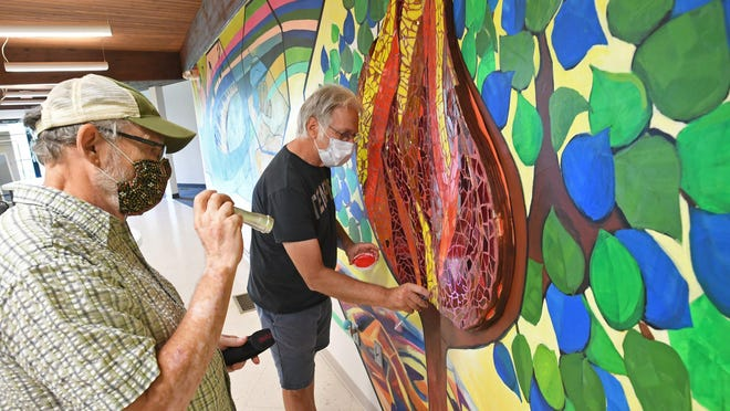 Artists Ed Grout, left, and Tom Ferraro complete a mural Thursday at the Unitarian Universalist Congregation of Erie in Millcreek Township. The 45-foot-long, 9-foot-tall mural features symbols and principles central to the Unitarian Universalist faith.