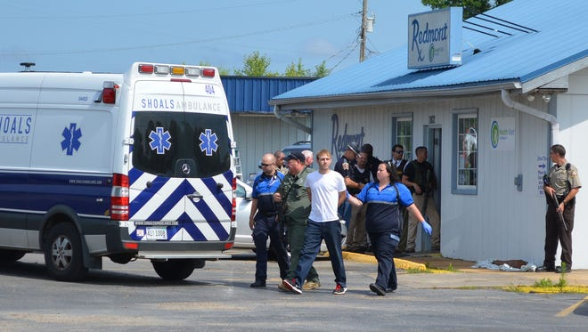 Authorities escort a suspect from Redmont Pharmacy, in Red Bay, Ala. on Tuesday, June 8, 2015 after a standoff with police. The Franklin County sheriff says a hostage situation has been resolved the pharmacy after the pharmacist convinced the gunman to hand over his weapon.