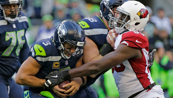 Seattle Seahawks quarterback Russell Wilson (3) protects the football as he is sacked by Arizona Cardinals outside linebacker Chandler Jones, right, in the first half of an NFL football game, Sunday, Dec. 31, 2017, in Seattle. (AP Photo/John Froschauer)