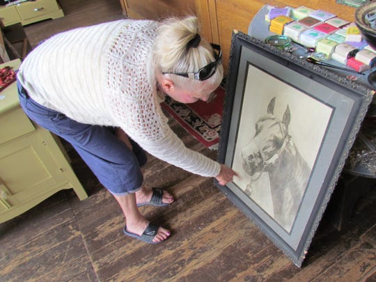 Terry Crawford of Christmas Valley points out nuances, such as the older style of tack on the horse, sketched into an agreeable piece of art she found at The Red Bench in downtown Silverton.