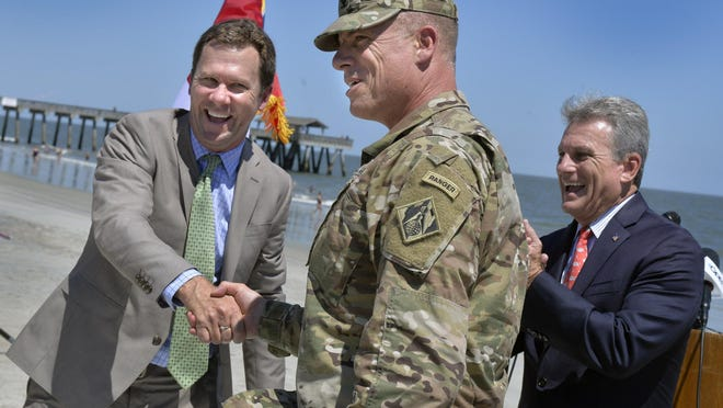 Mayor Jason Buelterman shakes hands with Colonel Daniel Hibner with the Army Corps of Engineers after signing a project partnership agreement on Tybee Island re-nourishment Thursday afternoon. Looking on is Congressman Buddy Carter, right.