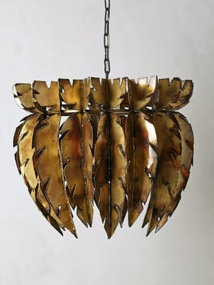 This photo provided by Anthropologie shows a chandelier crafted from brass feathers that makes a striking statement. (AP Photo/Anthropologie)