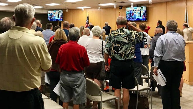 Marco Island residents and city councilors stand during the Pledge of Allegiance. The Marco Island City Council met at 5:30 p.m. Dec. 4.