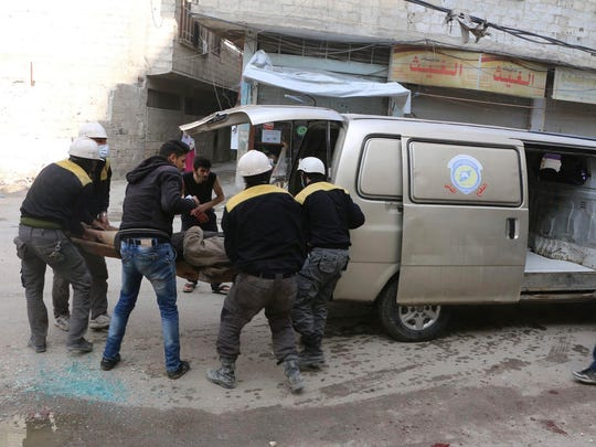 Members of the Syrian Civil Defense group carry a man who was wounded during airstrikes and shelling by Syrian government forces, in Ghouta, a suburb of Damascus, Syriain a photo released on Friday, Feb. 23, 2018 by the Syrian Civil Defense group known as the White Helmets. Syrian government warplanes supported by Russia continued their relentless bombardment of the rebel-controlled eastern suburbs of Damascus for a sixth day Friday, killing five people, opposition activists and a war monitor reported. The death toll from the past week climbed to more than 400.