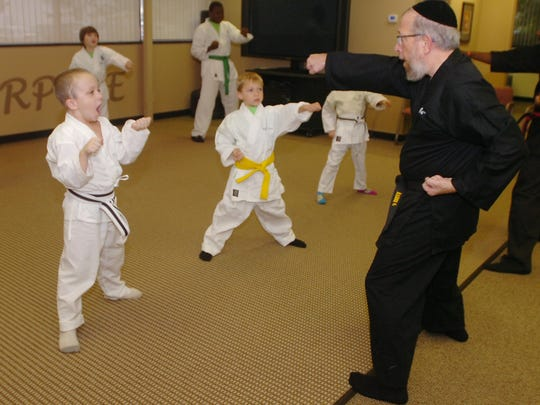 Rabbi Elimelech Goldberg teaches martial arts techniques to a group of students from Kids Kicking Cancer.