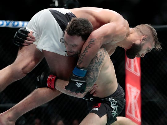 Frankie Edgar, bottom, lifts Jeremy Stephens during a featherweight mixed martial arts bout at UFC 205, Saturday, Nov. 12, 2016, at Madison Square Garden in New York. (AP Photo/Julio Cortez)